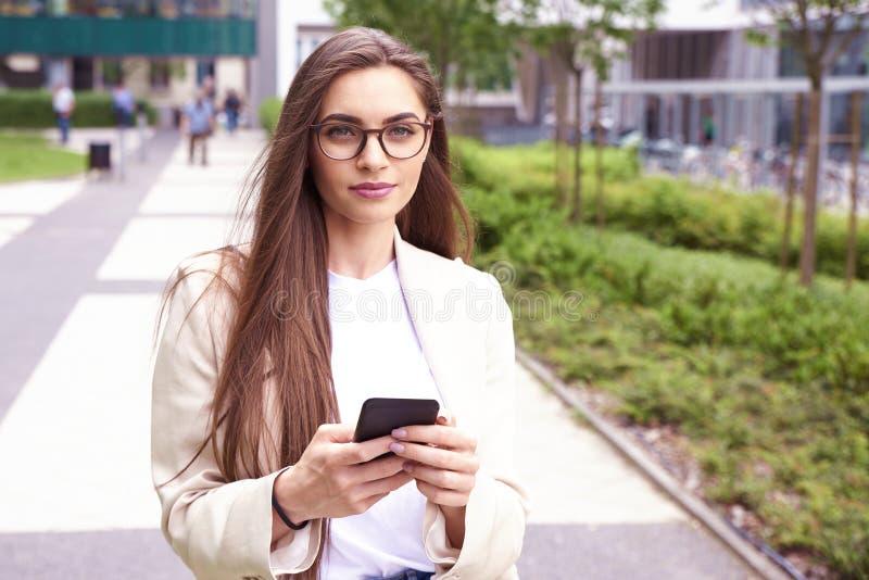 Envio de mensagem de texto novo da mulher de negócios ao andar na rua na cidade fotografia de stock