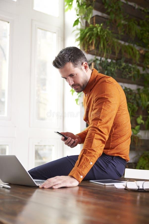 Envio de mensagem de texto ocasional do homem de negócios e portátil da utilização ao sentar-se no escritório e no trabalho fotos de stock royalty free