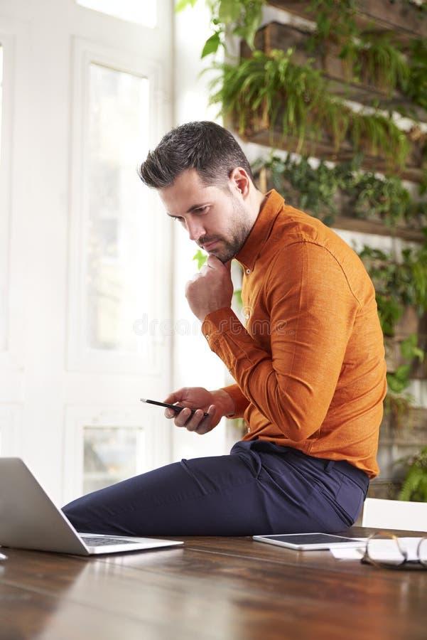 Envio de mensagem de texto ocasional do homem de negócios e portátil da utilização ao sentar-se no escritório e no trabalho foto de stock royalty free