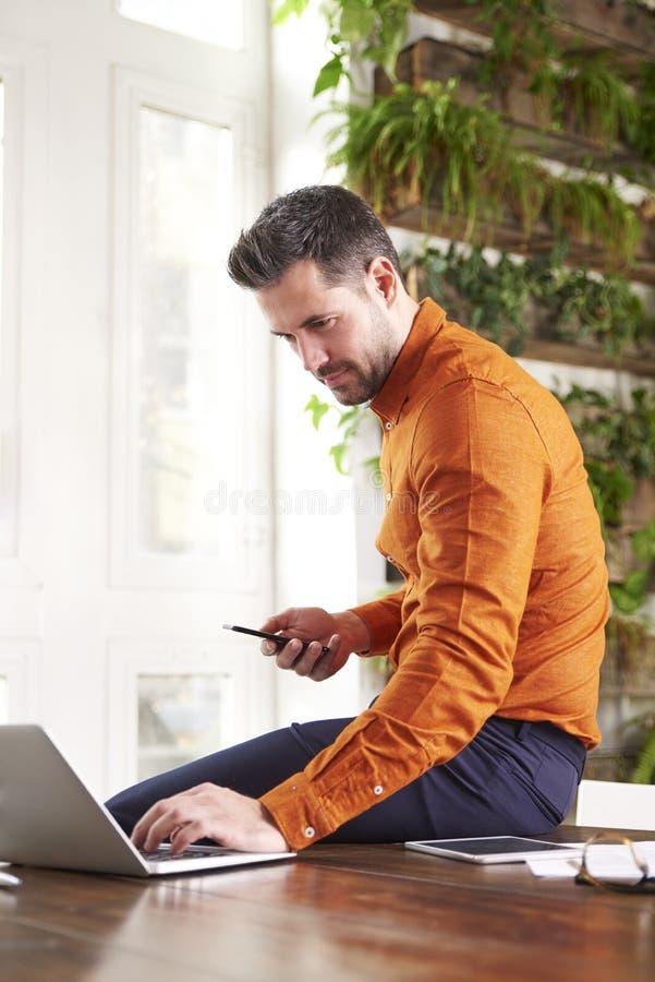 Envio de mensagem de texto ocasional do homem de negócios e portátil da utilização ao sentar-se no escritório e no trabalho imagens de stock