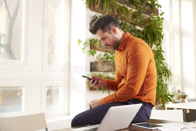 Envio de mensagem de texto ocasional do homem de negócios e portátil da utilização ao sentar-se no escritório e no trabalho fotografia de stock