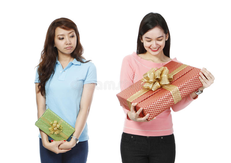 Envious of Bigger Gift. A young women holding a small gift, envious of the much bigger present of a friend (on white background royalty free stock images