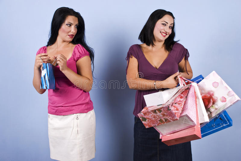 Envious woman. The woman in pink with little bag envy her friend wealth and success,but the rich woman it is vain and conceited and show a superiority look.Check