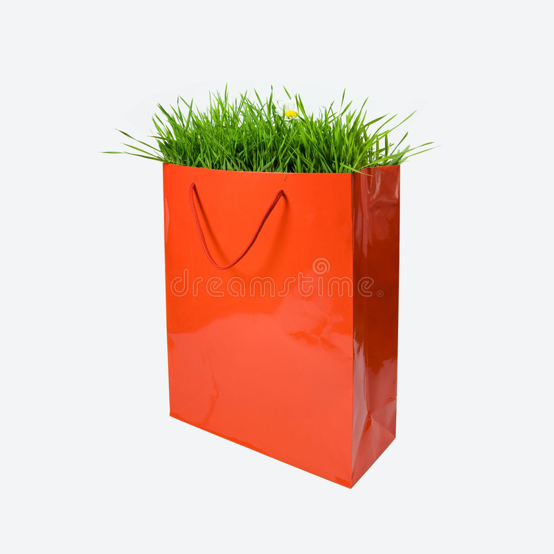 Environment Concept. Green grass in red paper bag stock photos