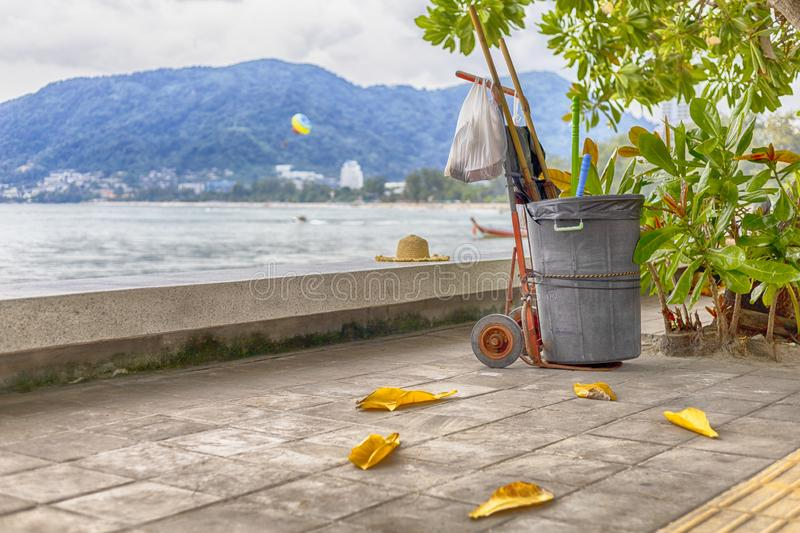 Black bin on Cart with dust pan and plastic garbage bag stay on sidewalk under the tree near the beach stock photos