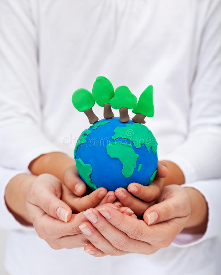 Environment and ecology concept. With clay earth and trees held in child and woman hands stock photos