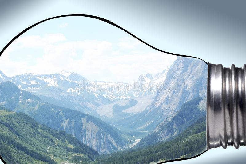 Environment, global warming and climate change concept: beautiful mountain panorama seen through a lamp bulb with copy space for y royalty free stock images