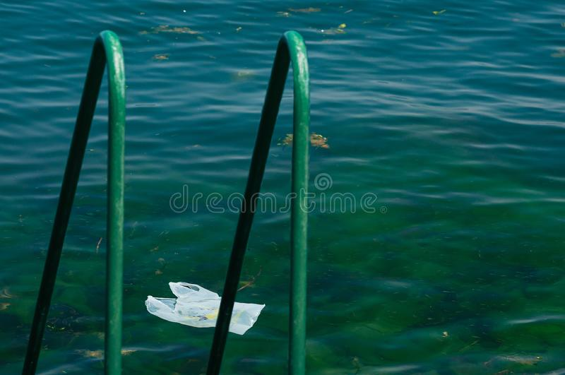 Environment pollution plastic problem. Plastic bag drifting on the sea surface, next to the beach with handhold for swimmers. Global problem of environment stock photos