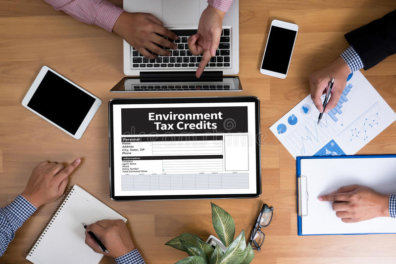 Environment Tax Credits Document Form Credits. Business team hands at work with financial reports and a laptop, top view stock photos