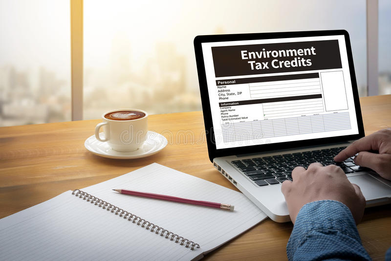 Environment Tax Credits Document Form Credits. Computing Computer flare sun, Cropped image male freelancer sitting at the table stock images