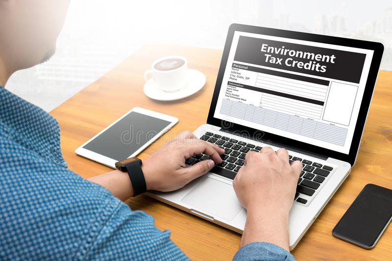 Environment Tax Credits Document Form Credits. Computing Computer flare sun, Cropped image male freelancer sitting at the table stock image