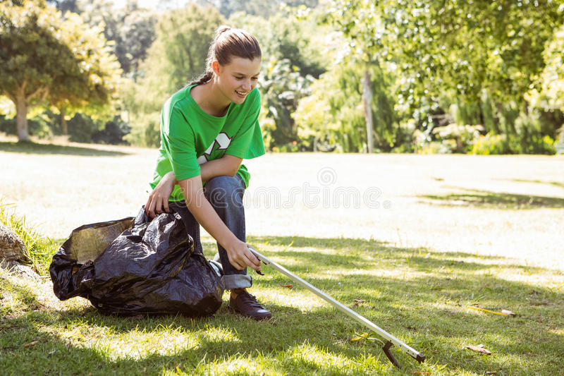 Environmental activist picking up trash. On a sunny day stock image