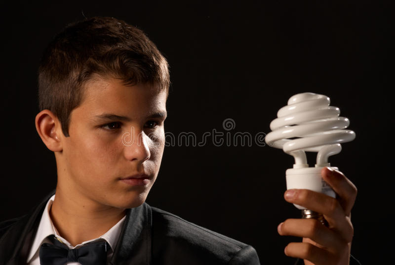 Environmental awareness. Teen holding a energy saving bulb royalty free stock image