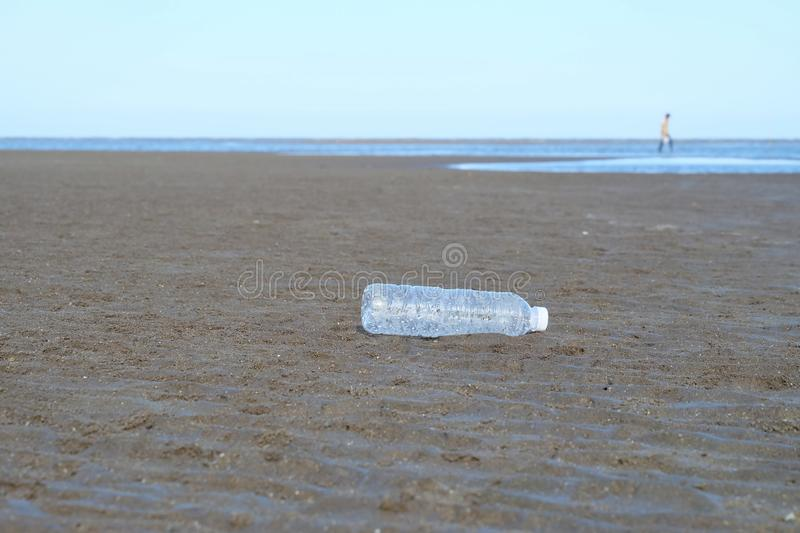 A plastic bottle of drinking water littering on the beach with sea waves background and a man walking on the area stock photography