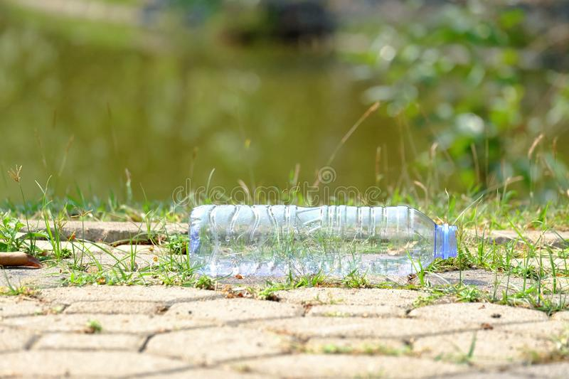 A plastic bottle of drinking water littering on cement pathway at the public park in the city with green nature and water source b royalty free stock photo