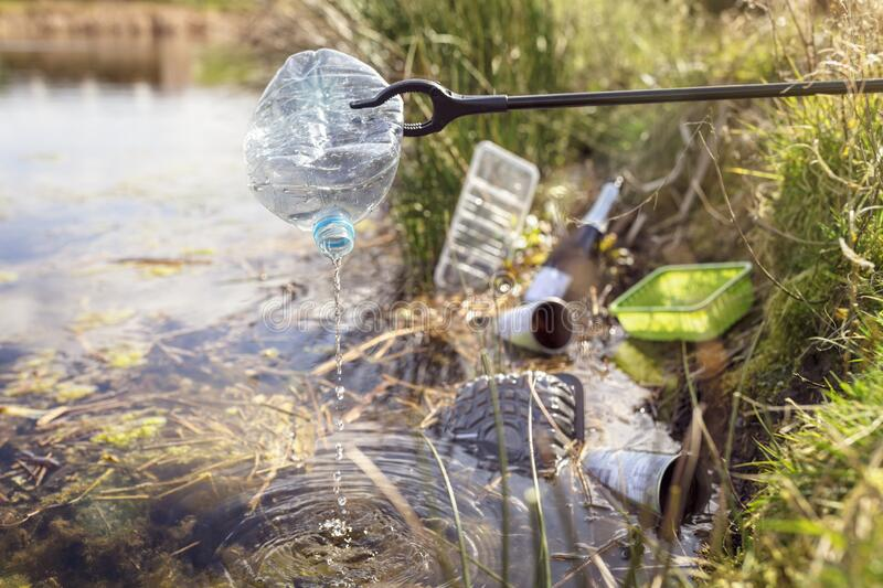 Environmental conservation collecting garbage and trash from water. Environmental conservation and pollution collecting garbage and trash from water royalty free stock photos
