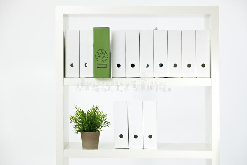 Environmental conservation in office. Conceptual image of environmental conservation, green folder with recycling symbol on a shelf full of white folders stock photography