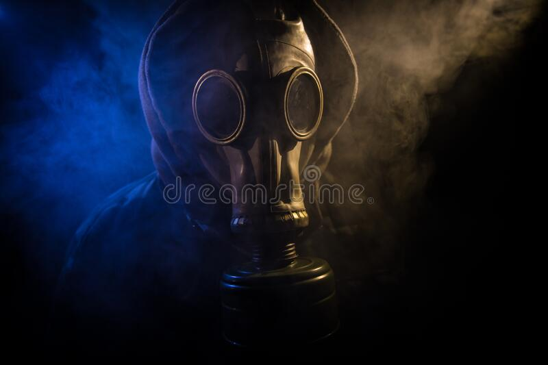 Gas mask with clouds of smoke on a dark background. Sign of radioactive contamination. Means for radiation protection. Danger of. Environmental disaster. Post stock images