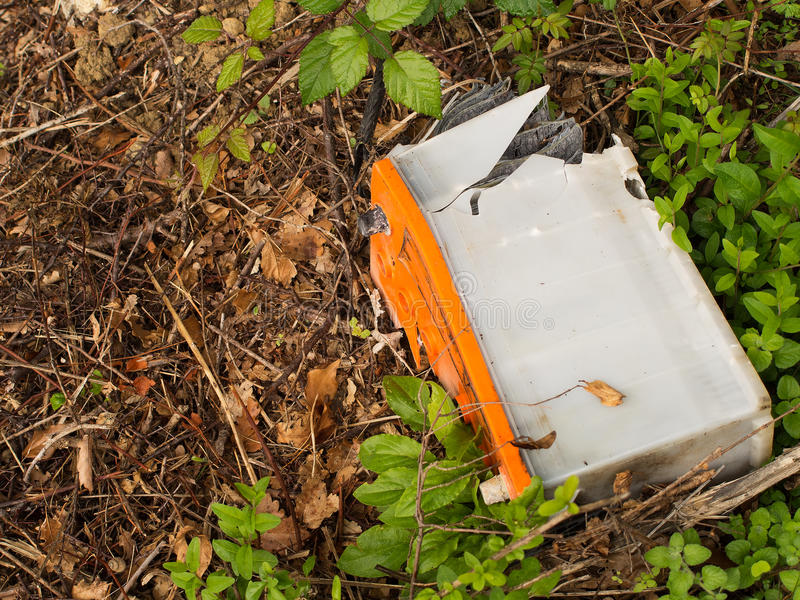 Environmental pollution, dumped old car battery. Old lead battery abandoned by the roadside royalty free stock image