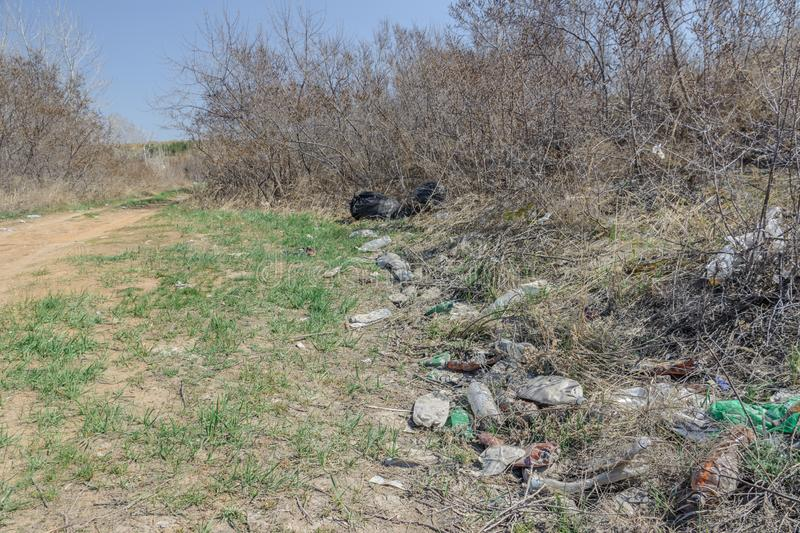 Environmental pollution. People left debris in wildlife. Garbage dump on the grass near the forest  polluting nature and city park stock image