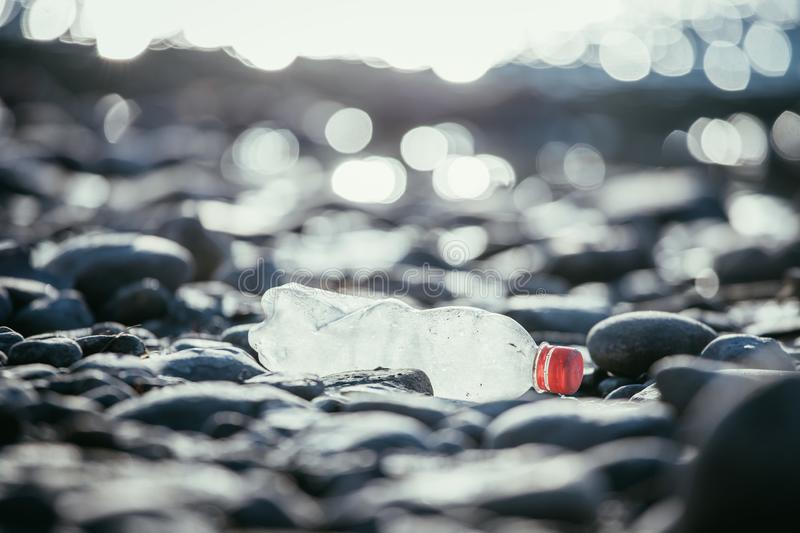 Environmental pollution: plastic bottle on the beach. Pollution waste plastic environmental protect bottle litter cleanup garbage trash sea beach pvc pet eco royalty free stock photos