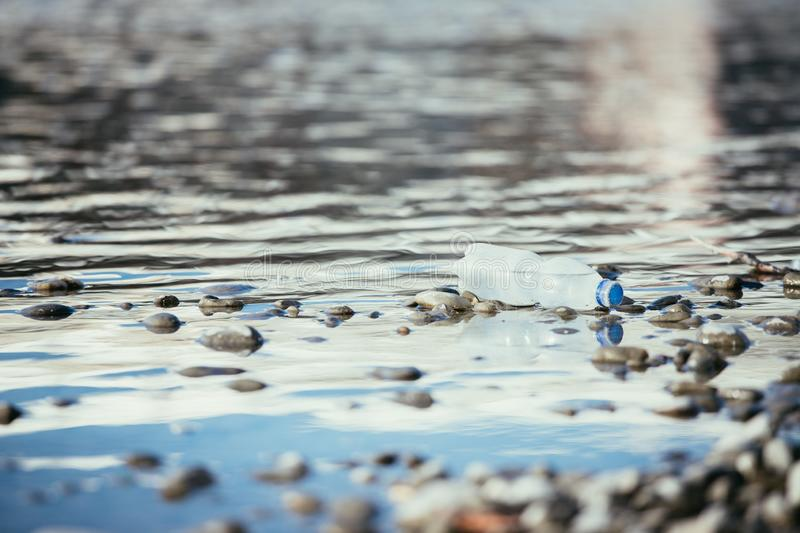 Environmental pollution: plastic bottle on the beach. Pollution waste plastic environmental protect bottle litter cleanup garbage trash water sea beach pvc pet royalty free stock photos
