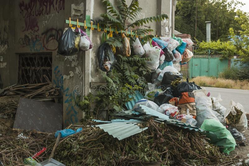 Environmental problem of the big city. Garbage collection for disposal by hanging on hooks mounted on the wall of the building. Garbage collection for disposal royalty free stock images