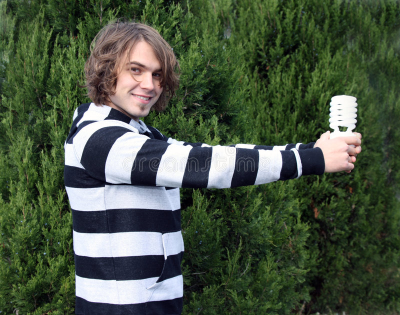 Environmentalist. Young male environmentalist, holding fluorescent bulb stock photo