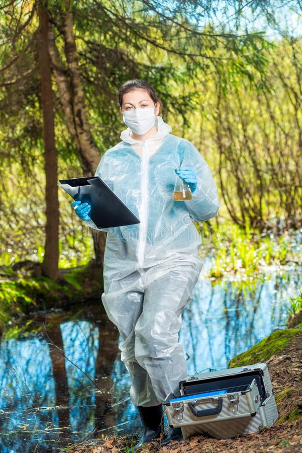Environmentalist biologist in the forest takes water samples. In the flask royalty free stock images
