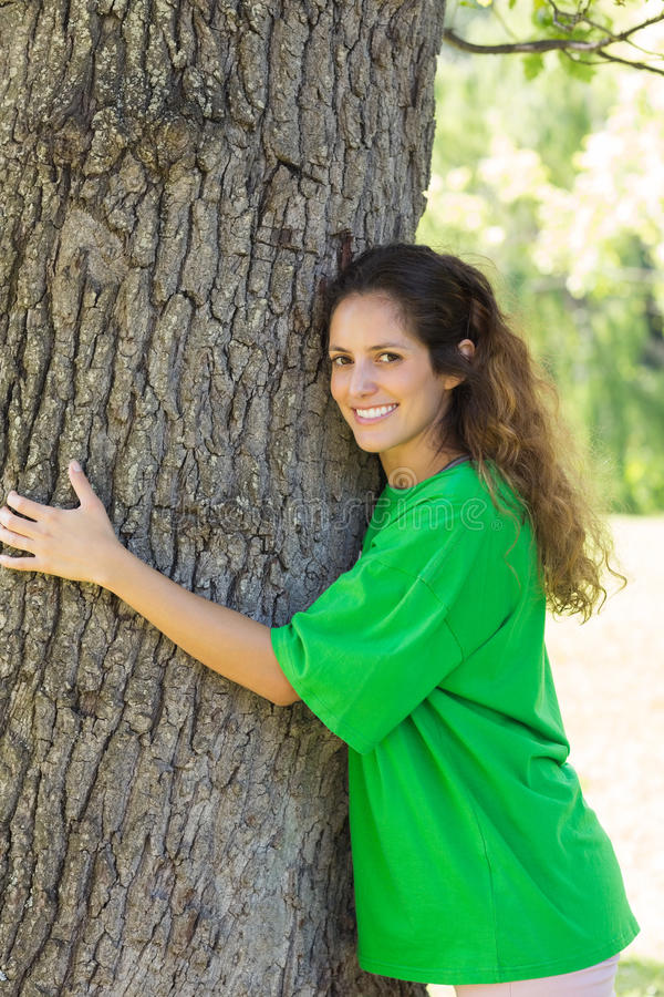 Environmentalist embracing tree trunk. Portrait of smiling female environmentalist embracing tree trunk in park royalty free stock photo