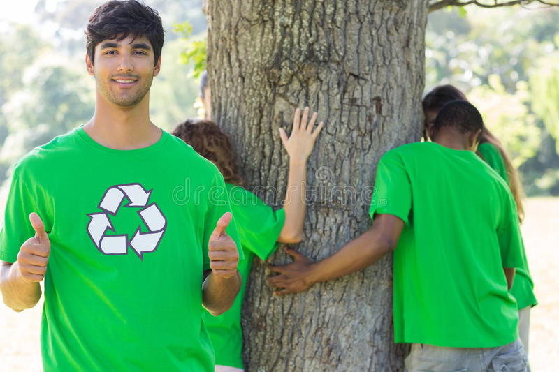 Environmentalist gesturing thumbs up in park. Portrait of confident male environmentalist gesturing thumbs up with friends hugging tree in background royalty free stock photography