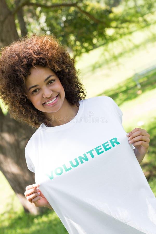 Environmentalist holding volunteer tshirt. Portrait of smiling environmentalist holding volunteer tshirt in park stock photography