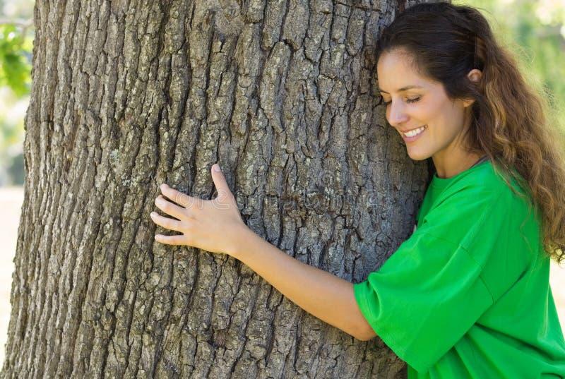 Environmentalist hugging tree trunk. Smiling female environmentalist hugging tree trunk in park royalty free stock photo