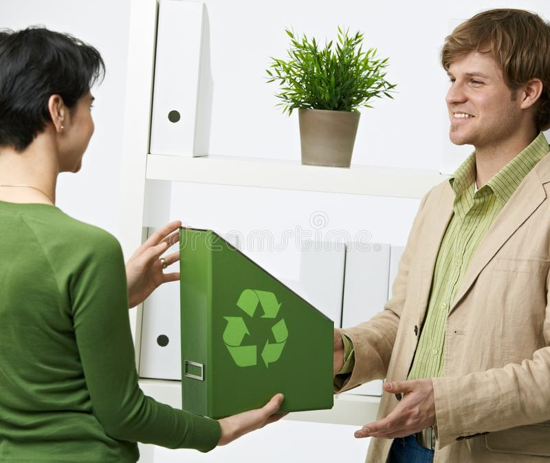 Environmentalist office. Happy office workers holding green folder with recycling symbol royalty free stock images