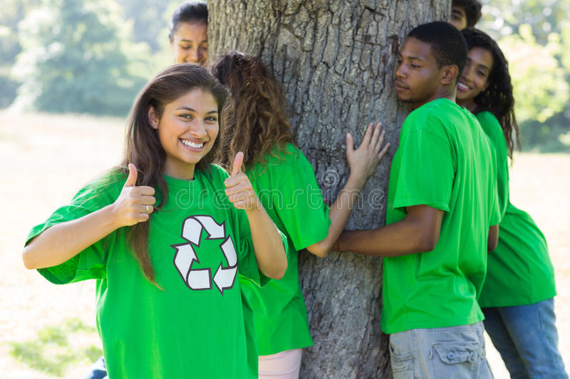 Environmentalist showing thumbs up. Portrait of confident female environmentalist showing thumbs up with friends hugging tree in background royalty free stock photo