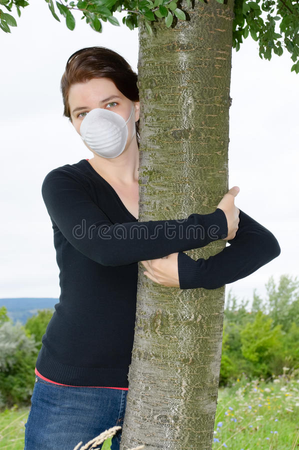 Environmentalist woman. Young environmantalist in face mask hugging a tree royalty free stock photography