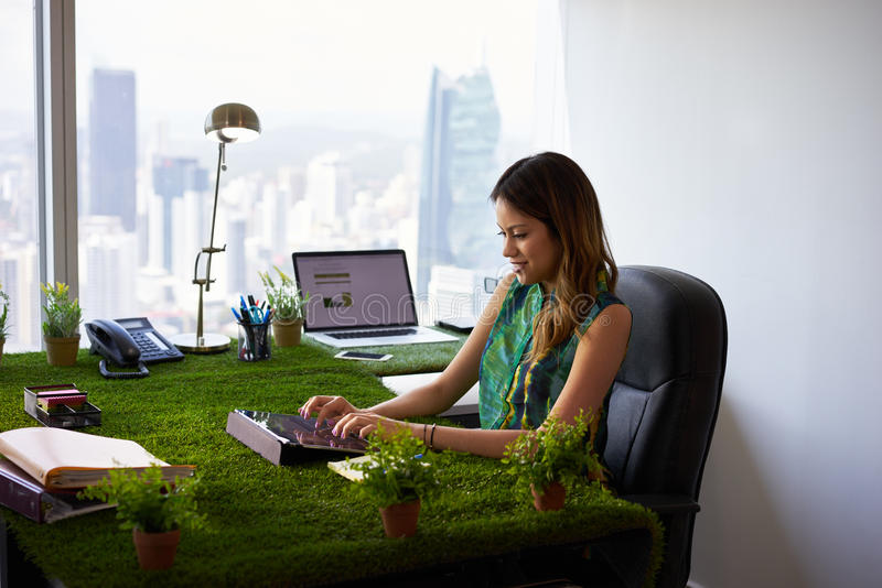 Environmentalist Woman Types Email With Tablet On Office Desk. Concept of ecology and environment: Young business woman working in modern office with table stock image
