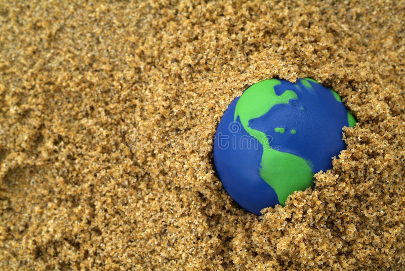 Environmentally Clean Earth. Earth day Background: Eco Friendly Blue and green planet earth buried in sand symbolizing environmental conservation of the world royalty free stock photos