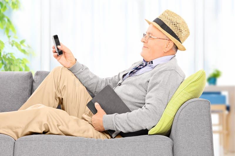 Envoi d'homme supérieur sms par l'intermédiaire du téléphone portable à la maison photo libre de droits