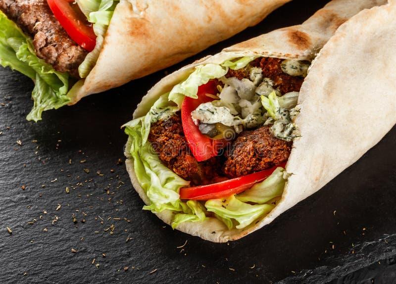 Envoltórios da tortilha com os rissóis do falafel dos grãos-de-bico, os legumes frescos e salada roasted no fundo de pedra preto  fotografia de stock
