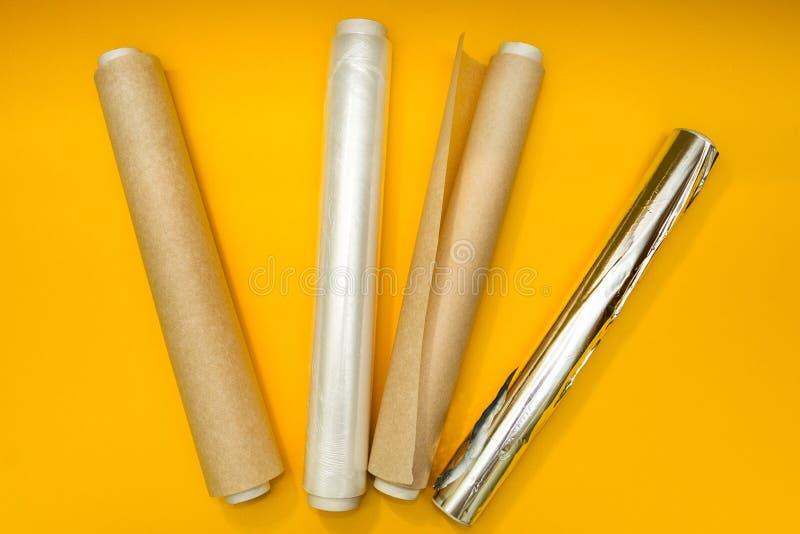 Envoltorio de plástico, papel de aluminio y rollo del documento de pergamino sobre fondo amarillo imagen de archivo libre de regalías