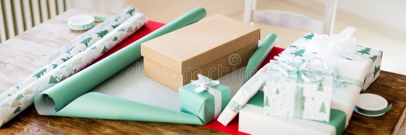 Envoltorio para regalos de DIY Regalos nórdicos hermosos de la Navidad en la tabla de madera La Navidad que envuelve la bandera d fotografía de archivo libre de regalías
