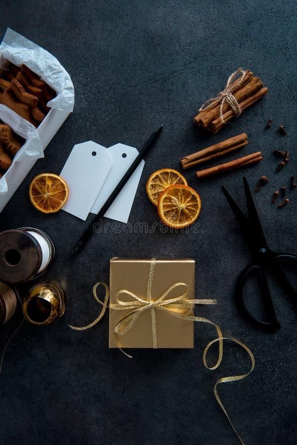 Envoltorio para regalos para la Navidad Tabla con el regalo en el papel del oro, compañero imagenes de archivo