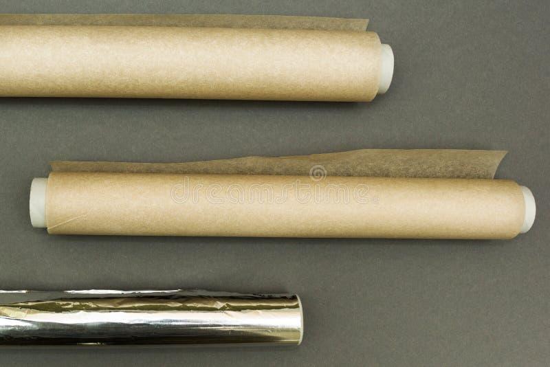 Envoltorios de plástico y rollo del papel de aluminio en fondo gris imágenes de archivo libres de regalías