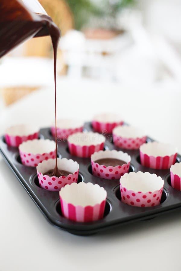 Envolturas rosadas de la magdalena que son llenadas de la pasta para las magdalenas del chocolate fotografía de archivo