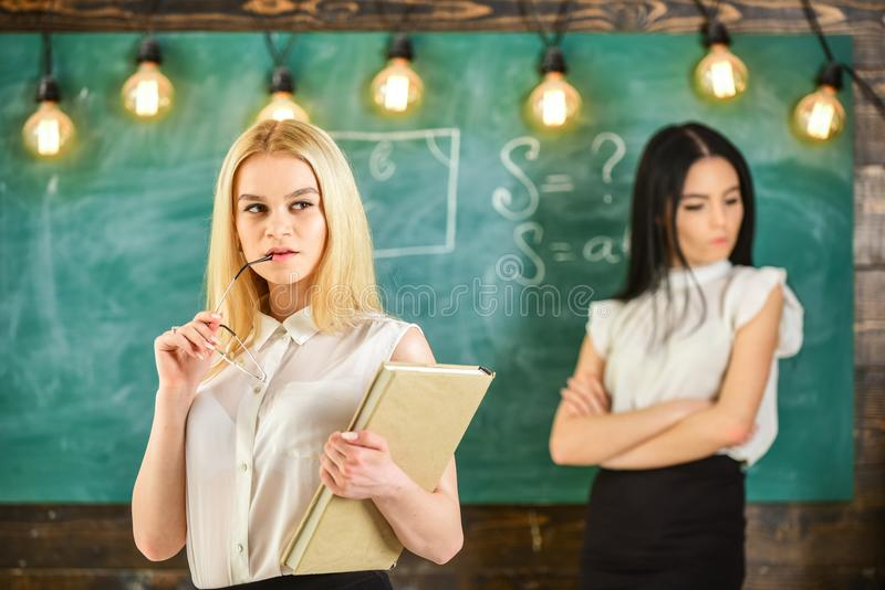 Envy and competition concept. Girl jealous of success of classmate in classroom, chalkboard on background. Woman with stock photography