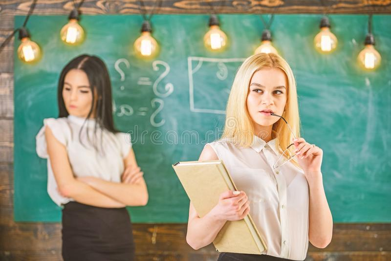 Envy and competition concept. Girl jealous of success of classmate in classroom, chalkboard on background. Woman with royalty free stock image