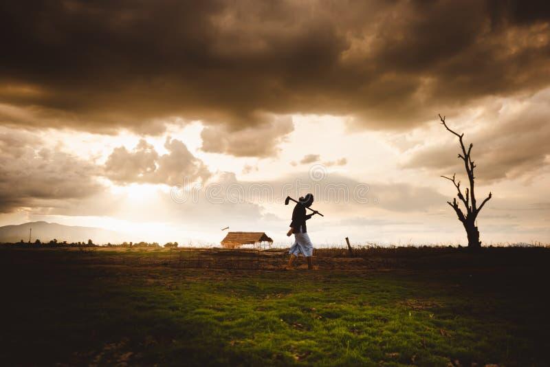 Enxada levando do fazendeiro impossível e só e passeio através de seu campo seco no por do sol Crise do aquecimento global foto de stock royalty free