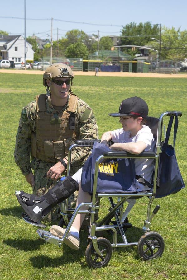 从EOD队的未认出的美国海军与在水雷对抗措施示范以后的未认出的孩子在舰队星期期间2014年 图库摄影
