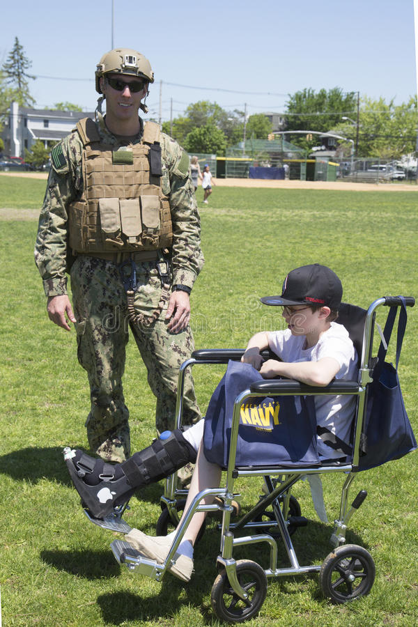 从EOD队的未认出的美国海军与在水雷对抗措施示范以后的未认出的孩子在舰队星期期间2014年 库存照片